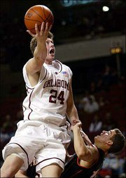 OU forward Matt Gipson collides with Princeton guard Ed Persia, right, during Saturday's game in Norman, Okla.