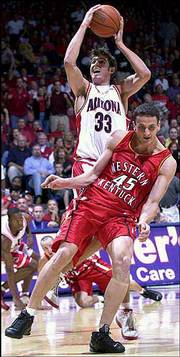 Arizona's Rick Anderson shoots over the misguided defense of Western Kentucky's Todor Pandov (45) during Saturday's game in Tucson, Ariz.