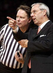 Kansas men's basketball coach Roy Williams chats with an official during Friday's game against UNC Greensboro