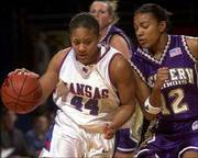 Kansas University's Aquanita Burras, left, drives past Western Illinois' Somer Easterwood. The Jayhawks fell to the Westerwinds, 48-46, on Saturday at Allen Fieldhouse.