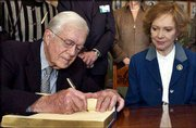 Nobel Peace Prize winner Jimmy Carter signs the guest book in the Nobel Institute in Oslo, Norway, as his wife, Rosalyn, looks on. Carter, 78, will be honored today for his decades of peace efforts throughout the world, especially his mediation of the 1978 Camp David peace accord between Israel and Egypt.