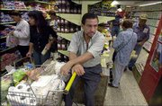 Venezuelan President Hugo Chavez faces increasing pressure from an opposition strike that has sparked economic shortages and choked oil exports. Rafael Villaran waited Monday for his wife at a supermarket in Caracas.
