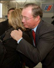 United Airlines CEO Glenn Tilton hugs a customer at United's terminal at Chicago's O'Hare International Airport. Tilton greeted customers and employees before and after addressing the media about the airline's Monday filing for Chapter 11 federal bankruptcy protection.