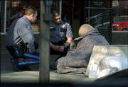 Lawrence Police officer Leo Souders talks with a homeless person on Massachusetts Street to see if he needed assistance getting to a shelter. More homeless are seeking Lawrence services, officials report.