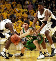 UW-Green Bay's Greg Monfre, center, pushes the ball away from Missouri's Jimmy McKinney, left, and Jefferey Ferguson during Monday's game in Columbia, Mo.
