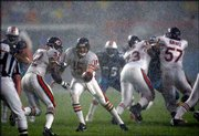 Chicago Bears quarterback Jim Miller (15) hands the football to running back Leon Johnson behind the blocking of Kevin Dogins (73) and Olin Kreutz (57) during a heavy rainstorm. The Dolphins defeated the Bears, 27-9, on Monday at Pro Player Stadium in Miami.
