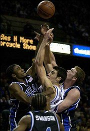 Kansas senior Nick Collison is sandwiched between Tulsa's Antonio Reed, left, and Jack Ingram, right, while fighting for a rebound. The Jayhawks survived a scare from the Golden Hurricane, 93-85, last December at Kemper Arena in Kansas City, Mo. Tonight the Jayhawks will travel to Tulsa for a rematch.