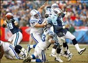 Titans quarterback Steve McNair (9) gets hit by Colts defenders after a pass to tight end Frank Wycheck (89) in this file photo from Sunday's 27-17 victory over Indianapolis. McNair needs only 12 yards passing and 76 yards rushing to become the fifth in NFL history to pass for more than 18,000 yards and rush for more than 3,000.