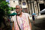 Cuban painter Manuel Mendive walks along the Plaza de la Catedral in Havana. Cuban's government emphasizes the promotion of art abroad.
