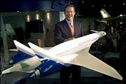 Alan Mulally, chief executive of Boeing's commercial airplanes division, shows a model of the Sonic Cruiser at the Paris Air Show. The show was June 19, 2001, at the Bourget airport, north of Paris. Mulally is expected to announce today that Boeing has decided to shelve plans for developing the jet, which could travel near the speed of sound, in favor of a more conventional, fuel-efficient plane the size of its 767 jet.