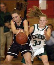 Lawrence High's Leigh DeBiasse, left, and Free State's Lauren Abney fight for a loose ball. The Lions hammered the Firebirds, 72-49, on Friday at LHS.