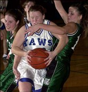 Perry-Lecompton's Jamie Amerine, center, takes a shot to the face from DeSoto's Lisa Lambert, right, while hauling in a rebound. The Wildcats won, 52-46, on Friday in Perry.