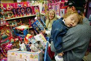 A tired Emilee Lane is held by her father, Jim, while her mother, Dalene, picks out toys at a Toy-R-Us store in Fresno, Calif. The couple found many bargains Sunday for their three children.