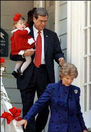 "Outgoing Republican Senate leader Trent Lott carries his granddaughter, Shields Armstrong, as he and his wife, Tricia, leave their home en route to church services in Pascagoula, Miss. Lott said Sunday that he had fallen into a ""trap"" set by his political enemies."