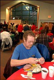 "Gordon Moore sits at one of the many tables at First United Methodist Church, site of the Free Community Holiday Dinner. ""I visit people I haven&squot;t seen in a while,"" Moore said as he enjoyed turkey, mashed potatoes and a full plate of hospitality served up by volunteers at the annual event Wednesday."