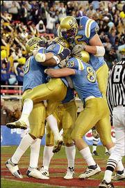 UCLA's Tyler Ebell (2) is mobbed by teammates after he scored a touchdown during Wednesday's Las Vegas Bowl in Las Vegas.