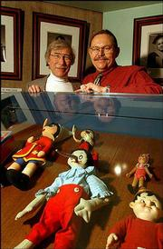 richard wunderlich, left, and Tom Morrissey pose with some of the Pinocchio artifacts on display in the Feinberg Library at Plattsburgh State University in Plattsburgh, N.Y. The two have co-authored a book about the evolution of the 1881 story of Pinocchio by C. Collodi into the Disney movie.