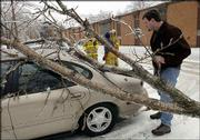 As Lawrence firefighters check a downed power line at Cedarwood Apartments, Glen Rossman surveys the smashed rear window on his 1999 Ford Taurus in this January file photo. Five inches of sleet and snow left many residents without power in January and forced Kansas University to close for only the ninth time in 30 years -- one of the memorable events of 2002.