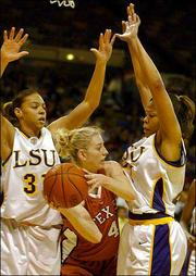 Texas' Kala Bowers (4) looks to make a pass as Louisiana State's Aiysha Smith, left, and DeTrina White apply pressure. The second-ranked Tigers trounced the No. 15 Longhorns, 76-58, Saturday at the Pete Maravich Assembly Center in Baton Rouge, La.