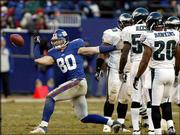 New York Giants tight end Jeremy Shockey flips the ball after a catch as the Philadelphia's Ike Reese and Brian Dawkins watch during Saturday's game in East Rutherford, N.J.