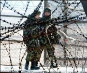 South Korean soldiers walk between fence and barbed wire as they patrol against the Imjingak Pavillion near the border village of the Panmunjom, South Korea. North Korea may be trying to pit South Korea against the United States.