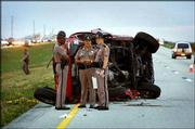 Police officers stand near a single-vehicle accident on Interstate 75 near Miami. Incoming Senate Majority Leader Bill Frist, a surgeon, stopped minutes after the rollover accident and helped tend to the four survivors until paramedics arrived. Two people were killed in the crash, including a 10-year-old girl.