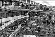 Inside the Anheuser-Busch bottling plant, the largest of its kind in the world, conveyors carry empty cartons, left, to the bottling area below in St. Louis in this 1965 file photo. The plant can package 3.8 million bottles and 5 million cans of beer a day and has an annual capacity of 7.2 million barrels.