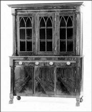 THIS BREAKFRONT BOOKCASE was made about 1835 in the Empire style. It has gothic-style glass doors. The 7 1/2-foot-tall piece is worth more than $7,000.