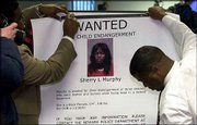 "Police officers hang a ""Wanted"" poster at a news conference in Newark, N.J., about the weekend discovery of the body of 7-year-old Faheem Williams, who was found dead in a storage bin, and his two brothers, who were found starving in a locked room. Sherry L. Murphy, shown in the poster, a 41-year-old go-go dancer entrusted with the care of her three young cousins, is being sought on child endangerment charges. Murphy is accused of beating and burning the three boys."