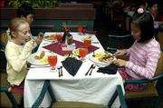 Hillcrest school fifth-graders, from left, Amber Steimle, Bao Tine and Truc Nguyen eat their dinner during the class field trip at Heartlands Restaurant at the Holidome.