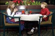 "Hillcrest school fifth-graders Sydney Keizer, 11, left, and Nate Rosenbloom, 10, make small talk before dining with their classmates at Heartlands Restaurant at the Lawrence Holidome, 200 McDonald Drive. The class took a ""dining out"" field trip, where the students learned about manners."