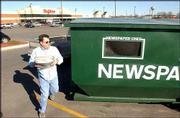 Hy-Vee Food and Drug Store, 4000 W. Sixth St., plans to open a gasoline station in its parking lot, approximately where this newspaper recycling bin is. John Hickey, Lawrence, recycled some papers Friday at the site.