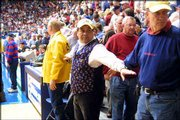 Volunteer usher Phil Ortega sports a Jayhawk vest as he clears the way for referees to leave the court at halftime of a recent Kansas University home basketball game. Ortega, who has been an usher at Allen Fieldhouse for 16 years, will be in his courtside spot when KU takes on Nebraska at 12:45 p.m. today.