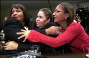 Relatives of inmate Madison Hobley react at DePaul University in Chicago after reading a copy of Gov. George Ryan's speech, in which he pardoned Hobley and three other death-row inmates. From left Friday are his sister, Robyn; his mother, Myra, and sister Penny.
