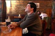 Jed Archuleta, Lawrence, enjoys a cigarette Friday at Free State Brewing Co., 636 Mass. Smokers in Salina no longer can light up in restaurants in that city, but Lawrence city commissioners say they have no desire to enact a similar ban here.