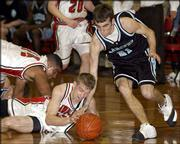 Lawrence High's Brian Seymour dives for the ball against Shawnee Mission East's Kyle Zeller, right. The Lancers defeated the Lions, 58-40, Friday night at LHS. Lawrence's Brandon McAnderson is at far left.