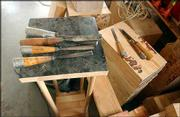 Chisels and gouges, the tools Harr uses to carve his wooden sculptures, lie idle in his studio.