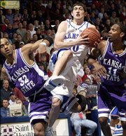 Kansas University's Kirk Hinrich, center, splits Kansas State defenders Gilson DeJesus, left, and Tim Ellis. Hinrich finished with 26 points in the Jayhawks' 81-64 victory over the Wildcats on Saturday at Allen Fieldhouse.