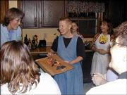 artist Mri Pilar, second from left, shows off a woodland-themed Rebarb during a recent party at the home of Lawrence resident Gayle Sigurdson, left. Looking on are 11-year-old Maude Thomas, center, Kay Runge and Sylvia Scoby, far right. Pilar developed the idea for the altered Barbie dolls during her stint as artist-in-residence in the Lucas-Luray school district.