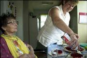 Ruth Mile puts whipped topping on a piece of pie for Josephine Bronczyk in Bronczyk's kitchen in Forest Lake, Minn. Moved to a nursing home against her will in July 2001, Bronczyk contacted an attorney and arranged to return to her home with round-the-clock care, using her own savings.