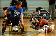 Rolling Rams' Dan Hill, left, watches as Kansas Wheelhawks' Linh Bowie falls chasing a loose ball. The Wheelhawks beat Hill's team from St. Louis, 65-52, Saturday at Holcom Recreation Center.