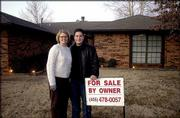 Erin and Jason Engelke stand in front of the home they recently purchased in Edmond, Okla. Record-low interest rates are prompting people in their early 20s to do something they hadn't thought possible at their age: buy a home.