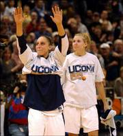 Connecticut's Diana Taurasi, left, acknowledges the crowd with teammate Ann Strother. The third-ranked Huskies hammered Georgetown, 72-49, Saturday at the Hartford Civic Center in Hartford, Conn., to set an NCAA Division I women's record with their 55th consecutive win.