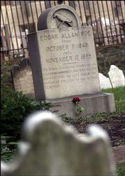 A lone rose rests against a marker at the original burial place of Edgar Allan Poe in Baltimore. A mysterious visitor left three red roses and a bottle of cognac in the old graveyard during the wee hours of Sunday on the famous writer's birthday, as has been done every year since 1949.