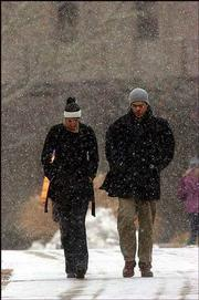Wednesday's snowfall found Kansas University students Courtney Hales, 19, Denver, and Philip Conway, 19, Kansas City, Mo., walking together across campus. About an inch of snow covered the ground by Wednesday evening. For more on the weather, see page 8B.