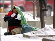 Robert Gilmore eats in front of Weaver's Department store, 901 Mass., as snow falls and temperatures drop during winter's coldest day. Gilmore lives on the streets and carries his possessions in plastic bags, which also include clothing and blankets provided by concerned Lawrence residents.
