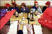 Members of the La La Lassies, a chapter of the Red Hat Society for women over 50, chat over coffee at Perkins Restaurant, 1711 W. 23rd St. The Lawrence chapter meets for lunch, participates in parades and even travels together throughout the year.