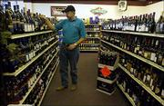 Joe Schmidtberger realigns bottles of wine at Alvin's Wine and Spirits, 905 Iowa. Schmidtberger supports the current law because it helps small businesses compete.