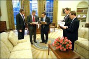 President Bush prepares his State of the Union speech with, from left, Dan Bartlett, White House communications director, Mike Gerson, director of presidential speechwriting, and speech writers Matthew Scully and John McConnell in the Oval Office. Bush will go before Congress and a worldwide television audience Tuesday night for his annual address.