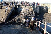 Palestinians surround the remains of a destroyed bridge in Beit Hanoun in the Northern Gaza strip. Israeli forces early Saturday used dynamite to destroy the bridge, which they said was used by militants to fire rockets at Israeli towns.
